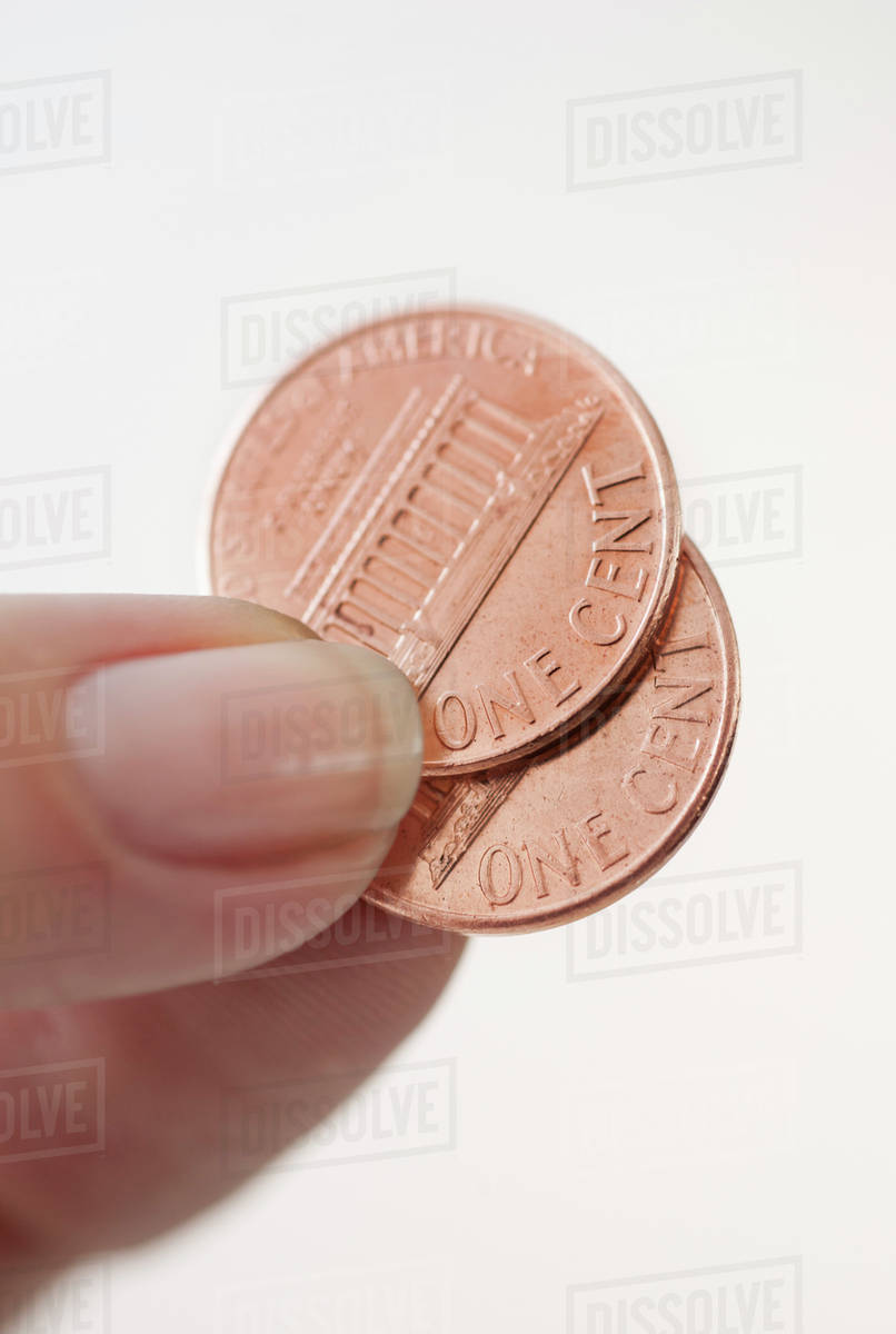 Studio shot of woman holding two one cent coins stock photo