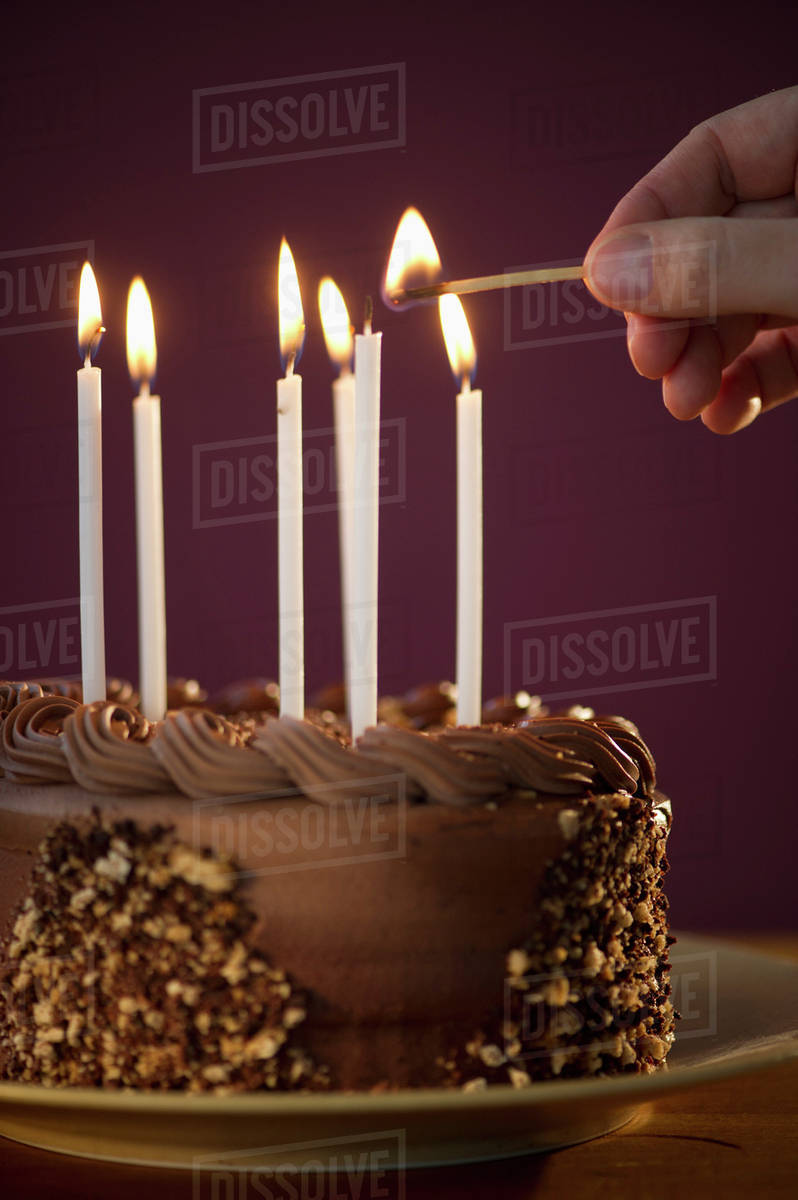 Studio Shot Of Man Igniting Candles On Chocolate Birthday Cake Stock Photo