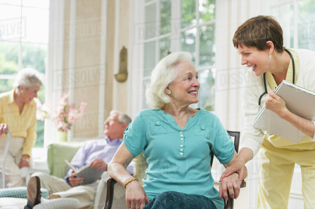 Senior Woman And Nurse Talking Outside Nursing Home Stock Photo Dissolve