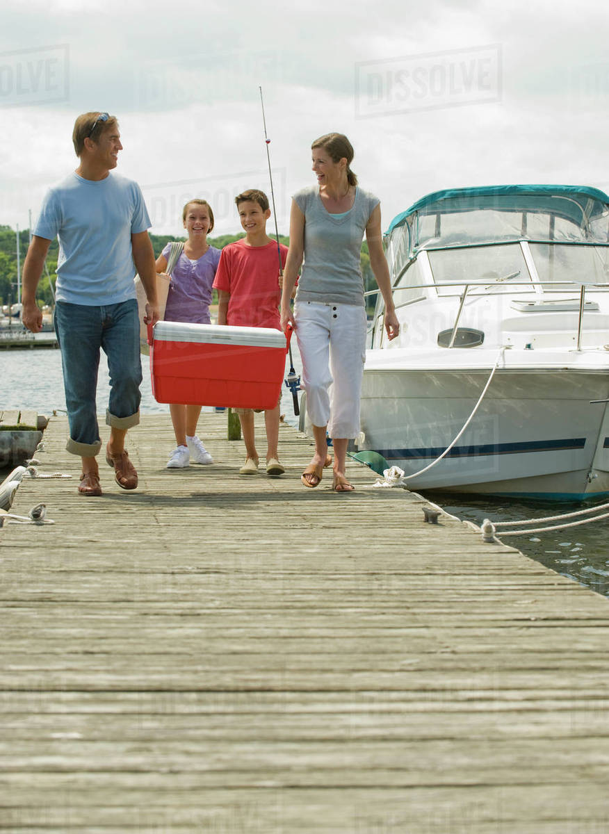 Family walking on boat dock with cooler Royalty-free stock photo