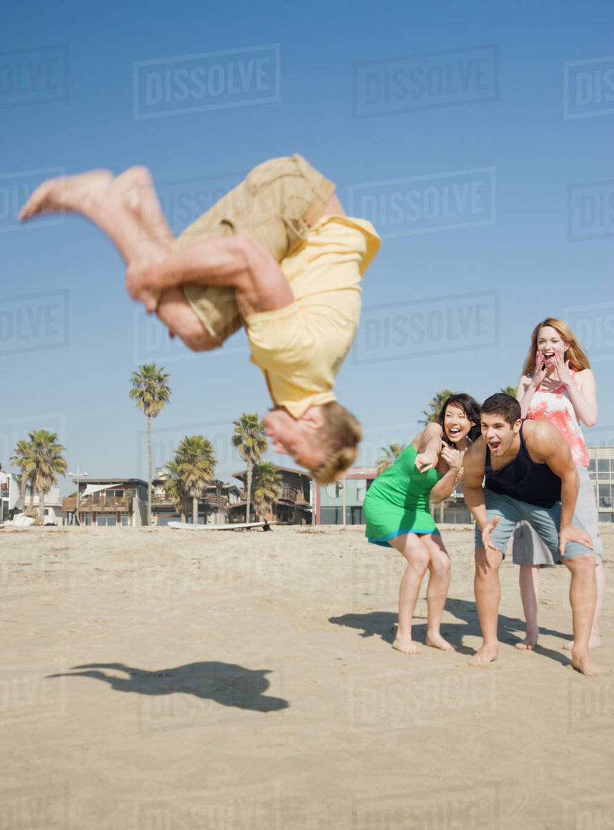 302028ce661103 Man doing back flip on beach - Stock Photo - Dissolve