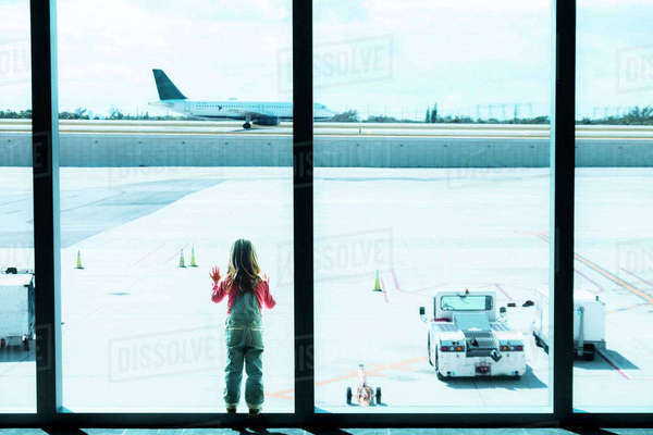 Girl (2-3) looking through window at airport Royalty-free stock photo