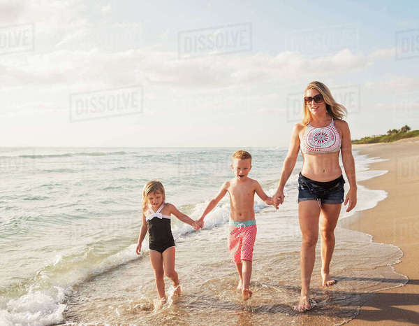 Mother walking with boy (6-7) and girl (4-5) on beach by water Royalty-free stock photo