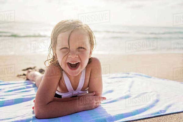 Girl (4-5) lying on beach laughing Royalty-free stock photo