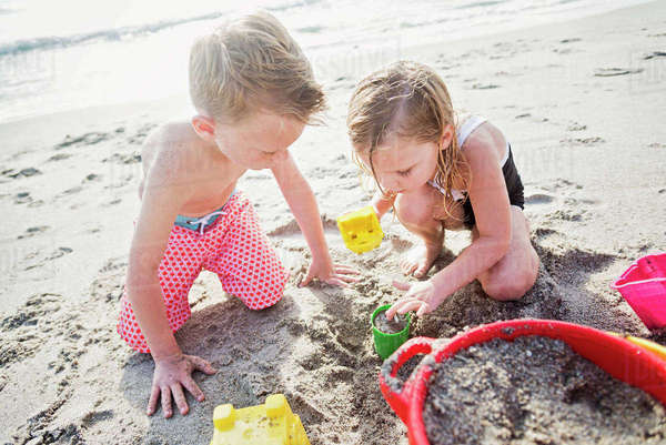 Boy (6-7) and girl (4-5) playing with sand on beach Royalty-free stock photo
