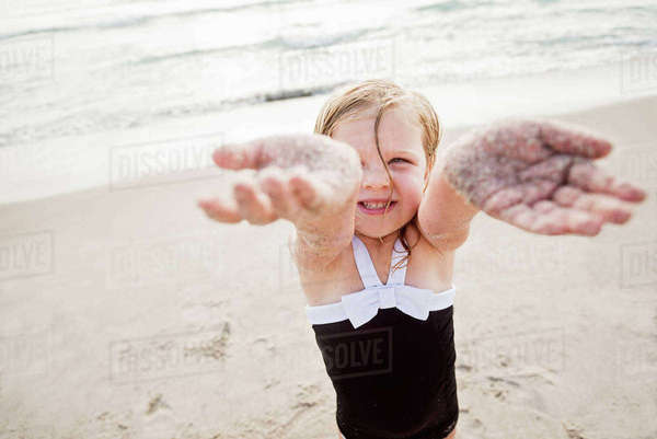 Girl (4-5) standing on beach showing her dirty hands Royalty-free stock photo