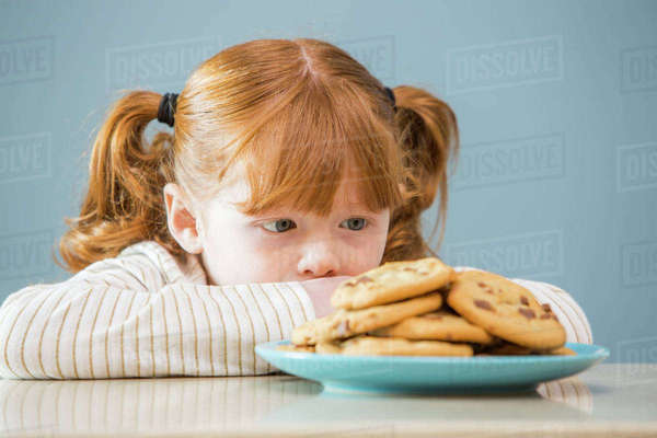 Girl (4 -5) looking on plate of cookies Royalty-free stock photo