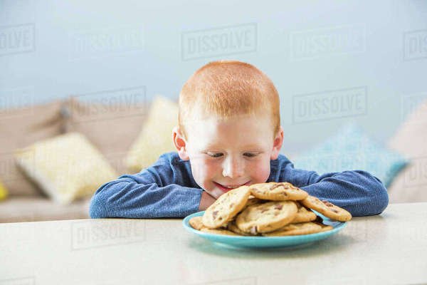 Girl (2-3) looking on plate of cookies Royalty-free stock photo