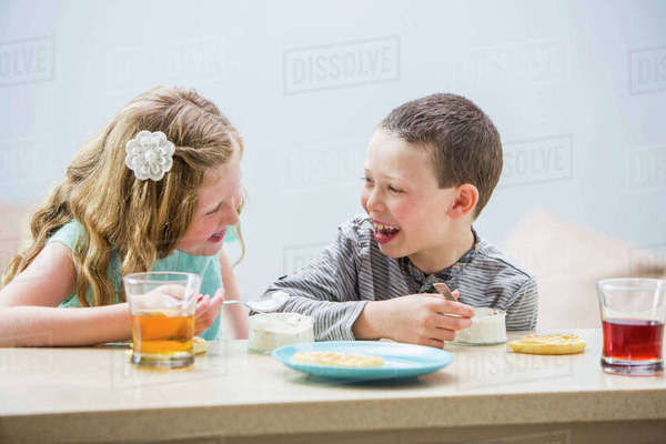 Smiling children (6-7, 8-9) eating pudding at table Royalty-free stock photo