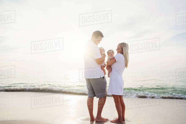 Happy family with two baby girls (2-5 months) at beach in sunlight Royalty-free stock photo