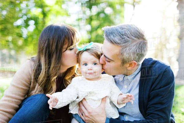 Portrait of parents kissing daughter (12-17 months) in park Royalty-free stock photo