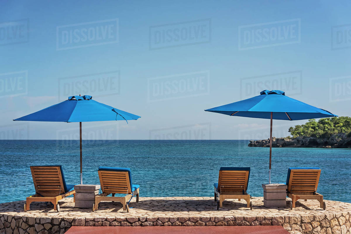 Jamaica Negril Beach Umbrellas And Lounge Chairs Against Tranquil Seascape
