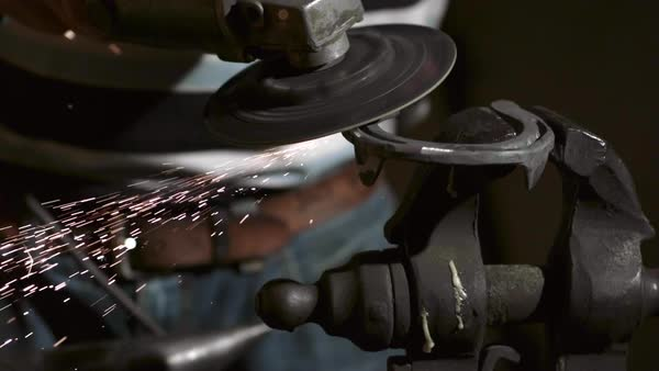 Close-up on horseshoe grinder throwing sparks. Royalty-free stock video