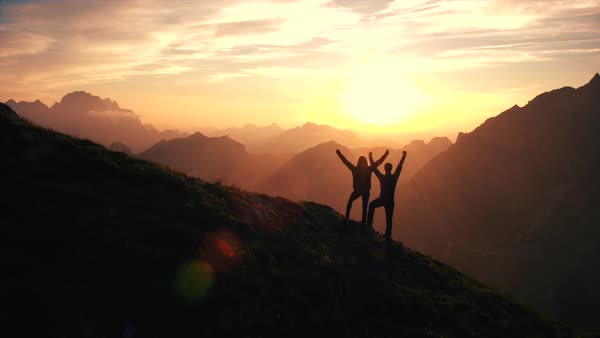 Rising above hiking couple celebrating successful climb on the mountain with raising arms at beautiful sunset Royalty-free stock video