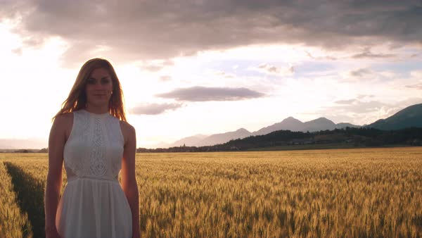 Jib shot - Young woman standing in the wheat field and looking into the camera Royalty-free stock video