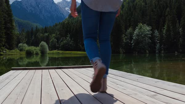 Behind woman walking on wooden pier at the lake Royalty-free stock video