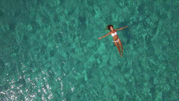 Aerial, beautiful young woman floating on water surface in crystal clear ocean Royalty-free stock video