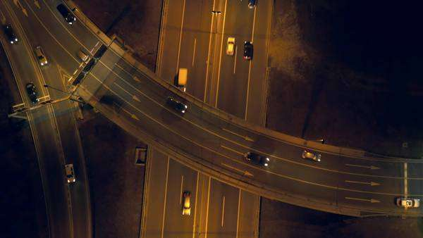 Aerial, vertical - Traffic at night. Roundabout over highway Royalty-free stock video