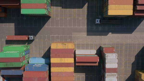 Aerial, vertical - Shipping containers and cargo trucks at port Royalty-free stock video