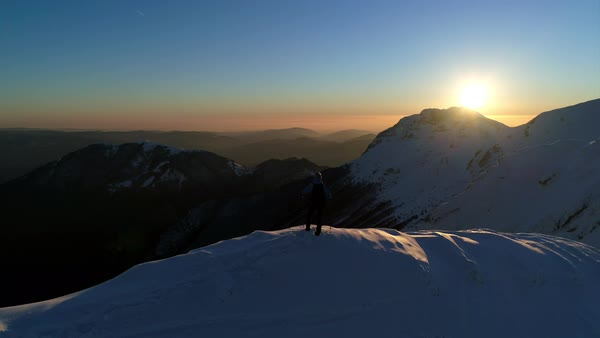 Aerial - Young male hiker standing on top of snowy mountain and looking at beautiful sunset Royalty-free stock video