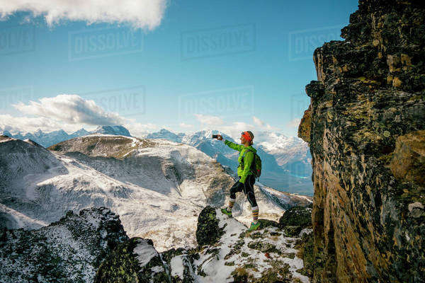 Woman takes picture from cliff edge of a mountain range. Royalty-free stock photo