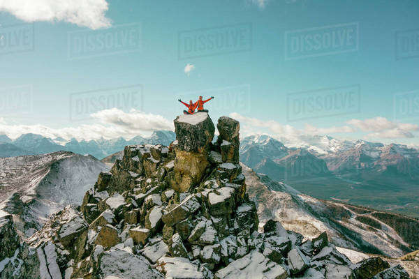 Two distant female hikers wave at the camera from the top of a mountain. Royalty-free stock photo