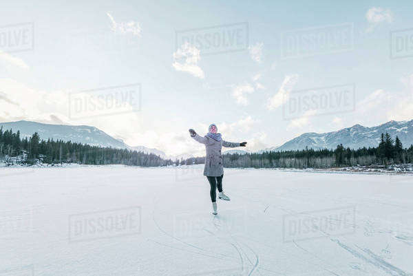 Woman skates on mountain pond towards camera. Royalty-free stock photo