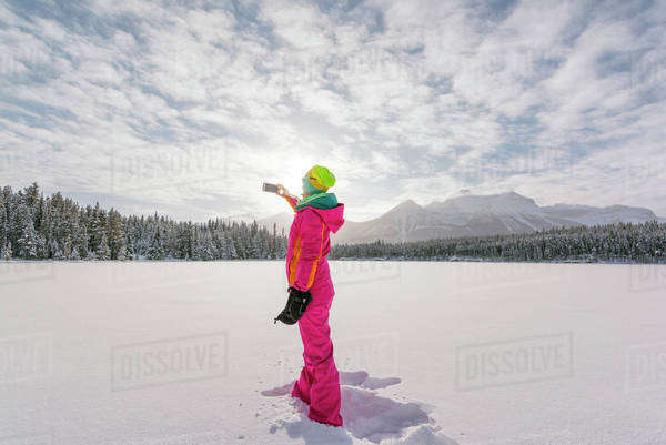 Woman takes cell phone photograph of a frozen mountain lake at sunset. Royalty-free stock photo