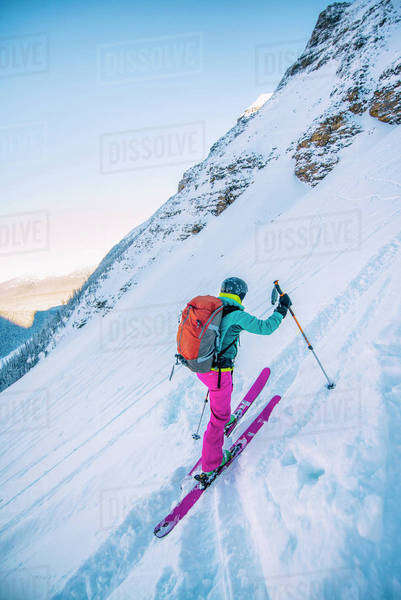 Female ski adventurer ascends a steep ski slope in the backcountry. Royalty-free stock photo