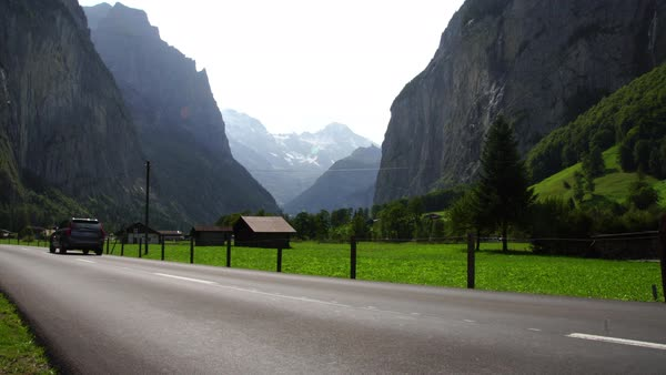 Cars drive the Jungfrau valley of Lauterbrunnen Interlaken Alps in summer in Switzerland  Royalty-free stock video