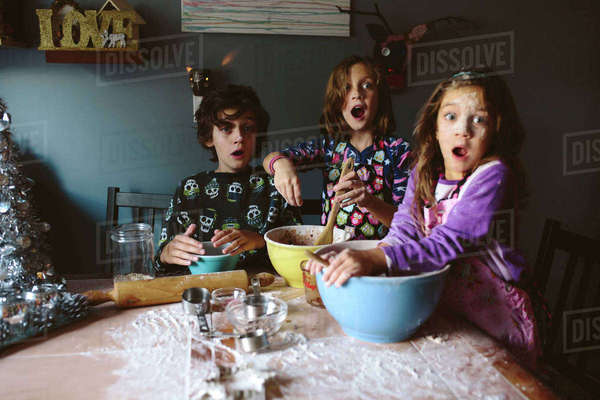 Surprised siblings looking away while making dessert at home Royalty-free stock photo