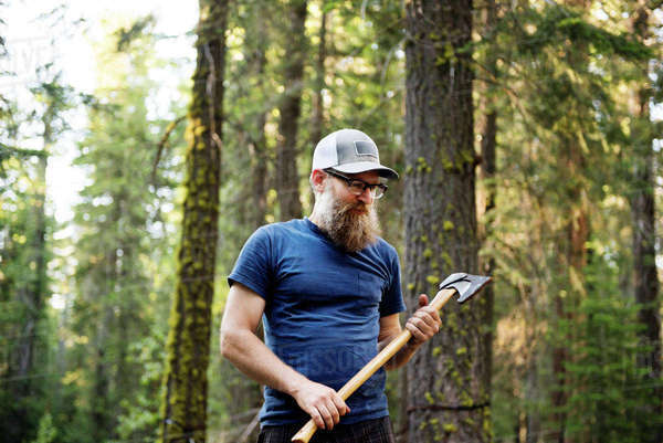 Mature man holding axe while standing in forest Royalty-free stock photo