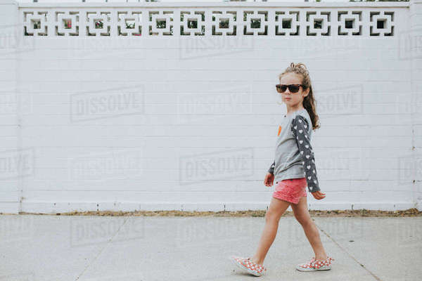 Girl in sunglasses walking on footpath Royalty-free stock photo
