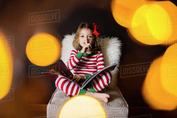 Portrait of cute girl with finger on lips and book sitting on chair at home Royalty-free stock photo