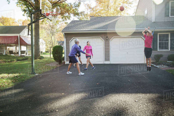 Family playing basketball at backyard on sunny day Royalty-free stock photo