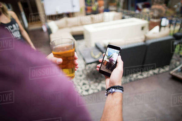 Cropped image of man looking at photograph in smart phone Royalty-free stock photo