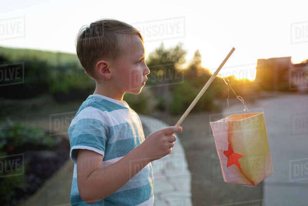 Side view of boy holding stick with paper bag Royalty-free stock photo