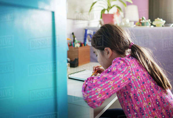 Side view of girl writing while sitting at table Royalty-free stock photo