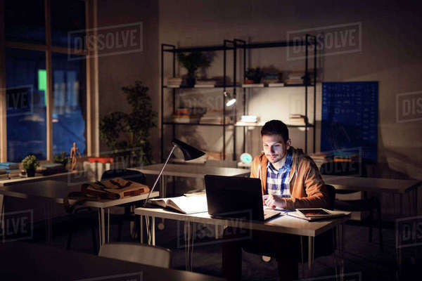 Confident student studying in library at night Royalty-free stock photo
