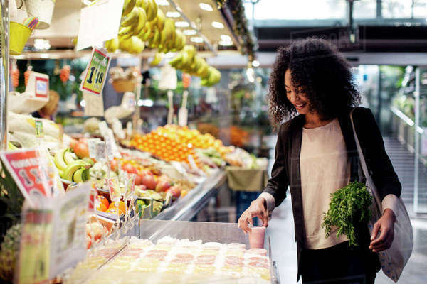 Woman buying juice while standing at store Royalty-free stock photo