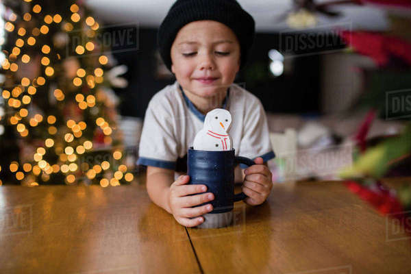 Cute boy holding cup with marshmallow snowman at table in home Royalty-free stock photo