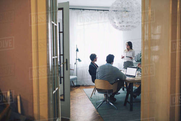 Business people discussing in office seen through doorway Royalty-free stock photo