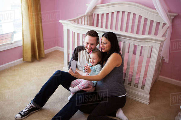 High angle view of family taking selfie while sitting against crib at home Royalty-free stock photo
