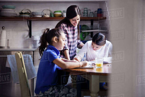 Woman looking at daughters studying seen through doorway Royalty-free stock photo