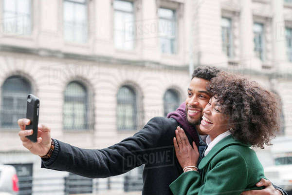 Business couple taking selfie while standing in city Royalty-free stock photo