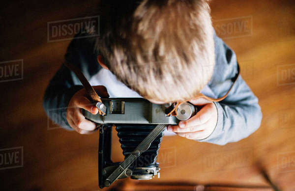 Overhead view of boy using vintage camera Royalty-free stock photo