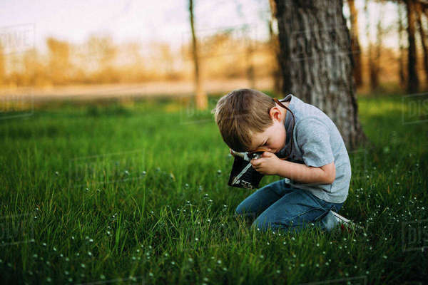 Side view of boy photographing through vintage camera Royalty-free stock photo