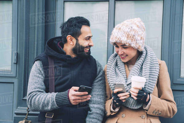 Happy man showing mobile phone to girlfriend while leaning by building Royalty-free stock photo