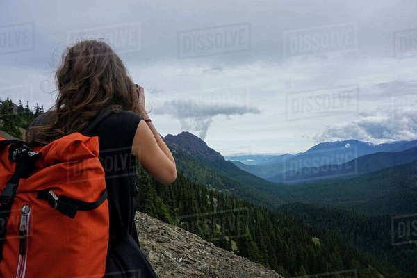 Rear view of female hiker standing on top of mountain against cloudy sky Royalty-free stock photo