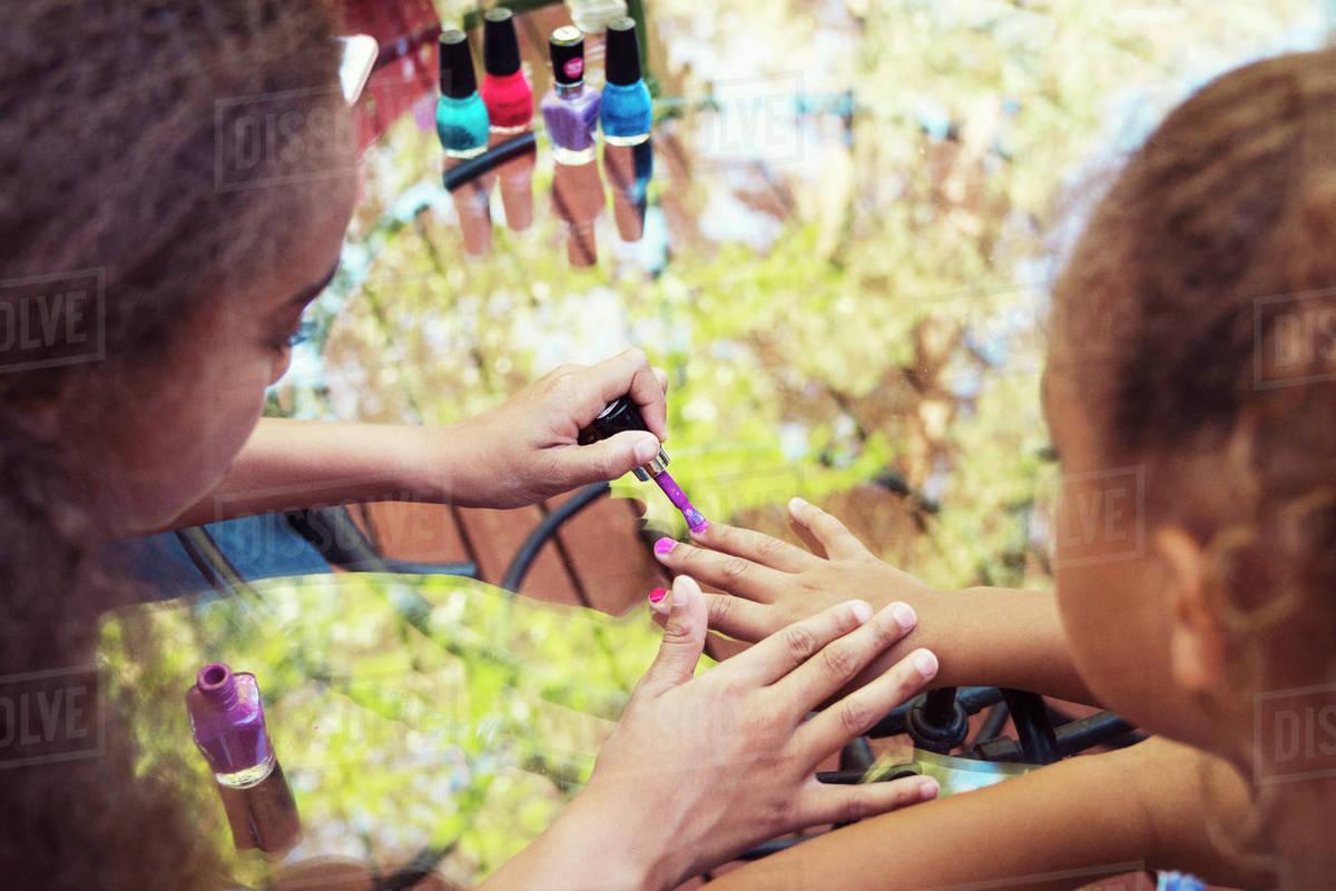 High angle view of girl applying nail polish on sister\'s fingernails ...